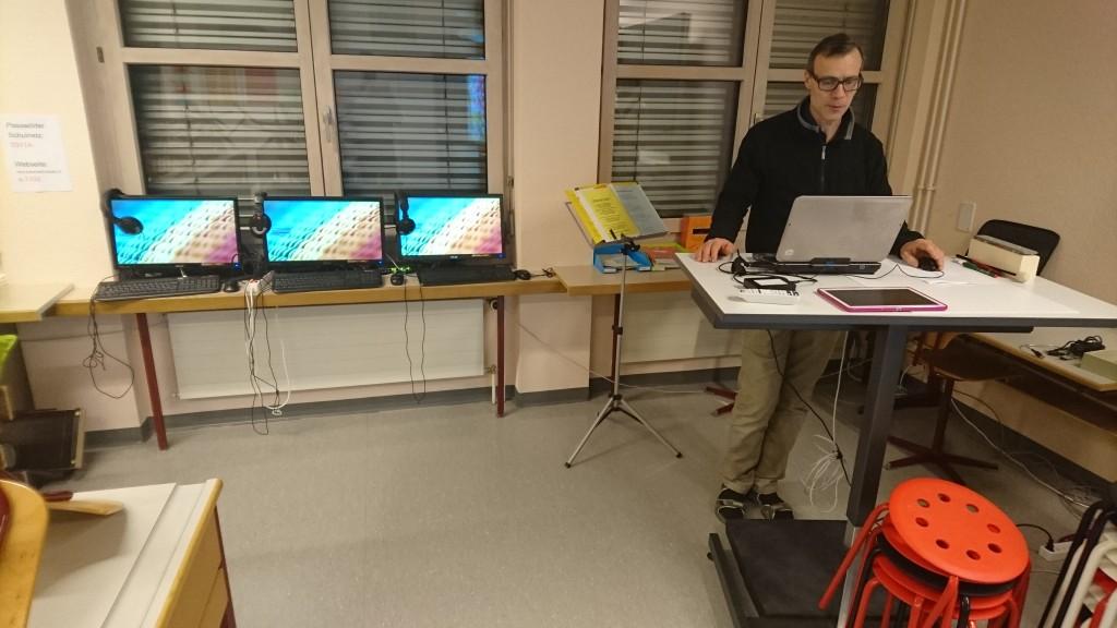 Rehtori Ueli Nick eräässä luokassa. Oppilaille on näyttöön integroituja tietokoneita luokan reunoilla, aina käyttövalmiina. Opettajilla on luokissa seisomapöytä perinteisen työpöydän sijasta.