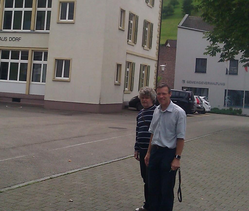 amXan Basil Stotz ja rehtori Ueli Nick Bubendorfin koulun alaluokkien rakennuksen edessä kesällä 2014
